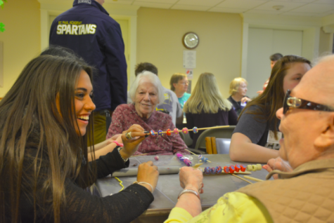 Senior Sami Brattland works with a partner at Lyngblomsten Retirement Community to make colorful clay beads. The beads will go to children with cancer or long-term illness around the country.