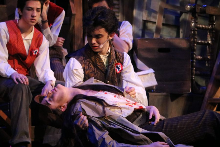 Marius (Justin Zanaska) holds Eponine (Taylor Reints) as she dies singing A Little Fall of Rain after being shot in battle.