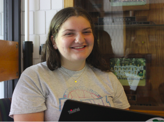 Freshman Annie Bottern moves from the library down to the couches in the Huss Center next to Trophy Cases.