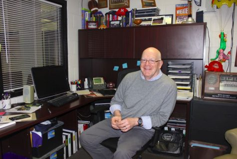 Assistant Director of Athletics Mike Brown sits at his desk, surrounded by memorabilia.