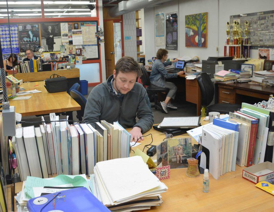 Upper School Mathematics teacher Carl Corcoran works at his desk in the math wing.