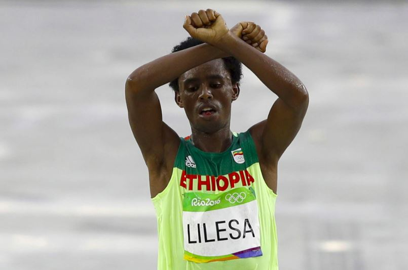 Olympic silver medalist, Ethiopian Feyisa Lilesa crossed the finish line with his arms above his head in the shape of an