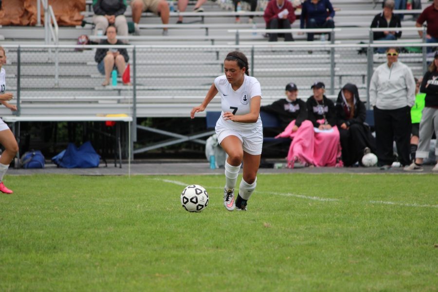 KICK IT! Senior Maggie Gallagher sprints to kick the ball up the field.
