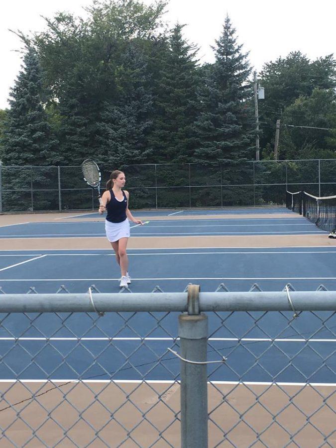 RUN AND HIT. Junior Isabel Brandtjen runs across the tennis court.