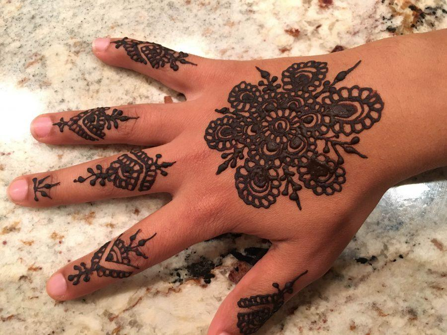 Senior Sarah Murad decorates her hand with henna on Eid al-Adha.