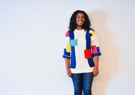 Junior Amina Smaller models a bright, geometrically printed sweater.