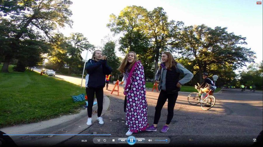 Sophomore volunteers Muriel Lang, Jennie Verhey, and Janie Brunell wave at the GoPro during RubicOnline Editor Mimi Gellers bike ride.