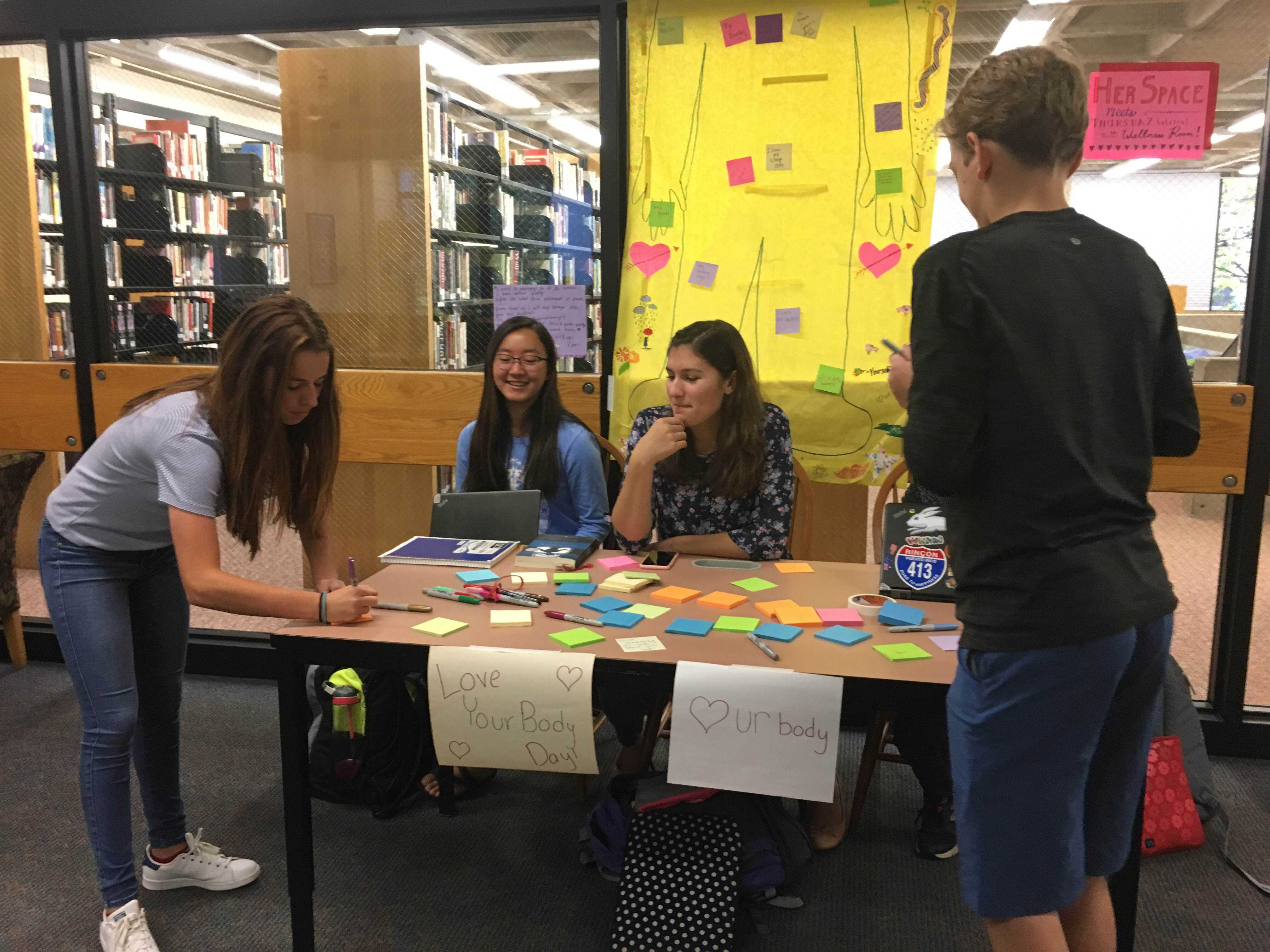 BODY LANGUAGE. HerSpace members junior Sky Li Griffiths and sophomore Isa Saavedra-Weis host members of the freshman class while they write post its to place on the Love Your Body poster.