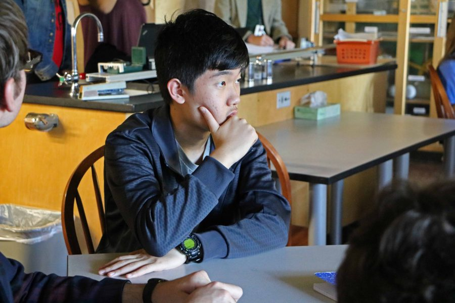 """FOCUSED. Ninth grader Allan Wang listens to slo-mo presentations in Physics class. """"[SPA is] totally different, like say here we change classes, but the teachers also change. In my school teachers change, but you're still sitting in one classroom, never move for the whole day,"""" Wang said."""