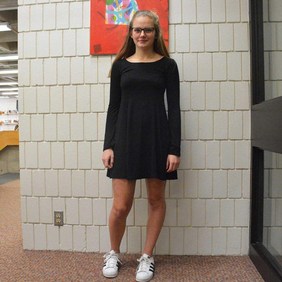 Sophomore Kaia Larsen shows off her monochromatic look of  a black dress and white Adidas sneakers.