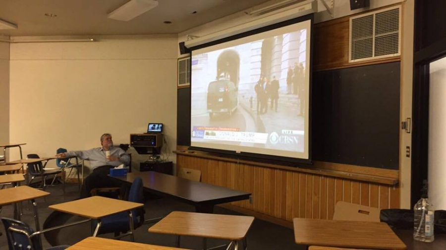Debate coach Tom Fones watches the lead up to the Inauguration  in the lecture room.