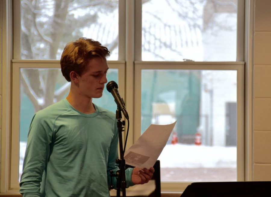 """Junior Robin Bartlett reads his own original piece of literature on Jan. 25 at the Iris: Art and Literature open mic night. """"It was a great experience to be here in front of my peers and my teachers and some of the faculty and to be able to share some of the work that I've worked so hard on producing. It felt really good to have my work appreciated by the community,"""" junior Robin Bartlett said."""
