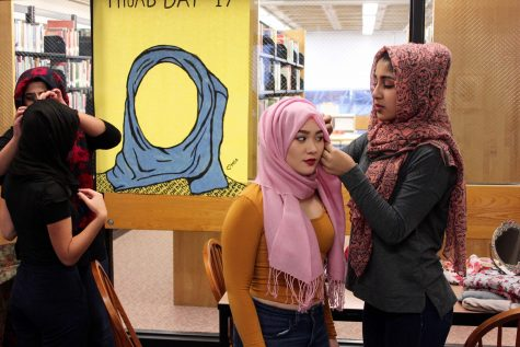 Members of Muslim Student Alliance help female students pin hijab on Feb. 1 for International Hijab Day.