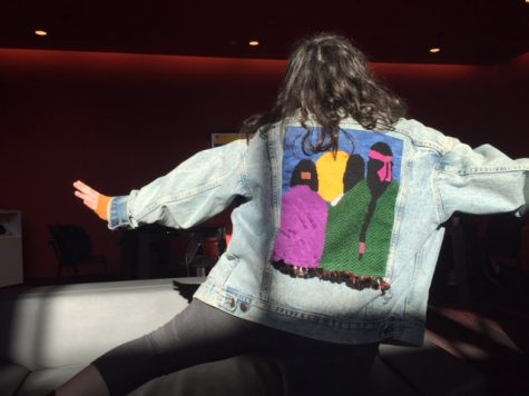 Junior Mira Zelle poses in her denim jacket with needlepoint done by her mother.