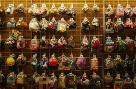 A wall in Unique Thrift Store holds plastic bags with dolls, yarn, fabric, and other items.