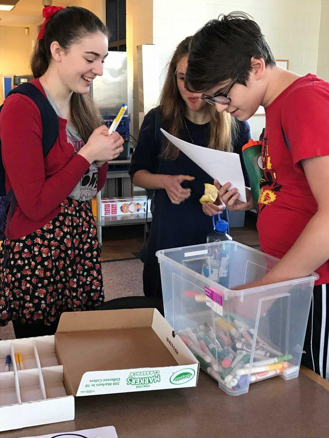 Senior Mary Grant, and juniors Flann Enneking-Norton and Jonah Harrison get markers and paper.