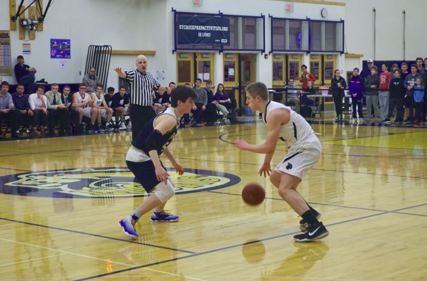 Senior Tommy Dicke dribbles around a defender at the Mar. 9 section quarterfinals game vs. St. Croix Prep.