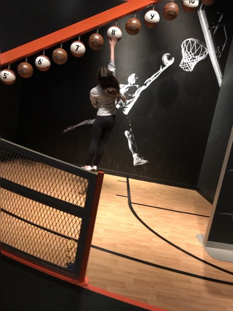 AIMING HIGH. Junior Marlee Baron reaches the eight-foot basketball at the Sportsology exhibit.