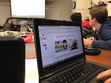 Students work on their presentations during Spanish class and learn tips from Senor Castellanos.
