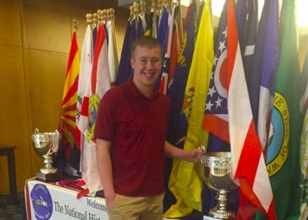 Junior Peter Blanchfield poses with the awards table at the National History Bowl.