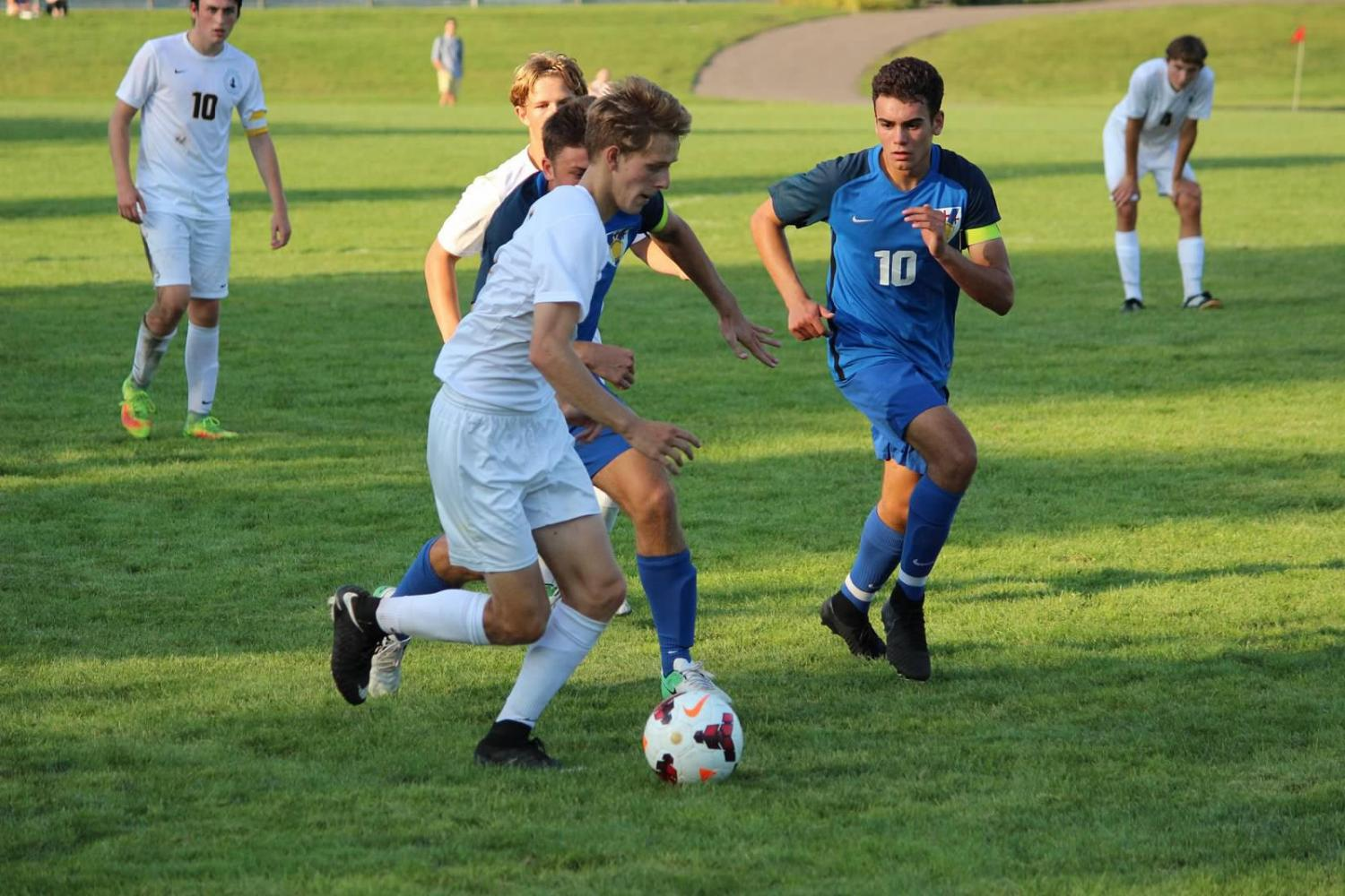 Co-captain Robin Barlett dribbles past a group of players during a game against St. Thomas Academy at Historic Lang Field.