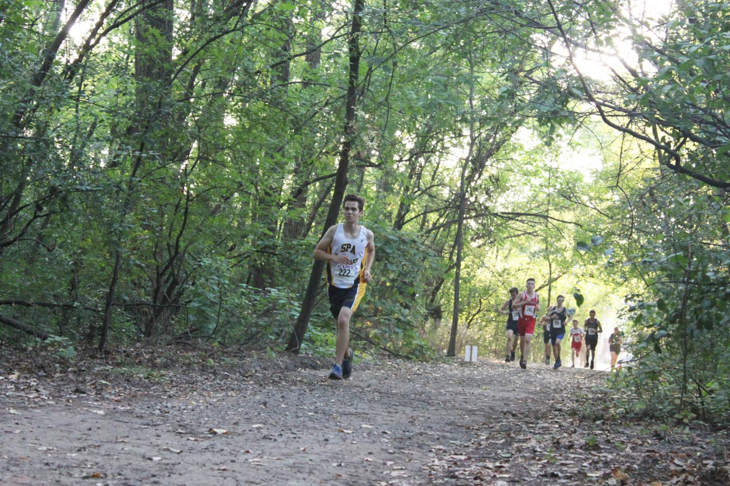 """Junior runner Will Rinkoff paces himself through a forest and ahead of the competition during a September meet. """"The feeling you get when you perform well in competition makes all the hard work you've done seem worth it,"""" co-captain Jonah Spencer said."""