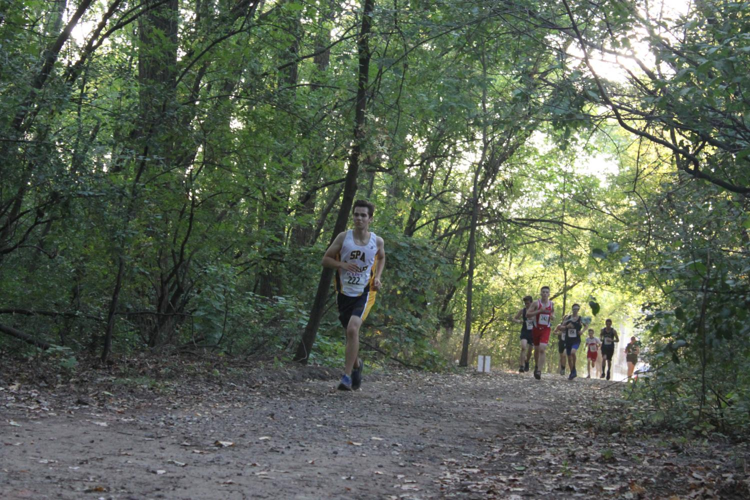 """YOUTH MOVEMENT. Junior runner Will Rinkoff paces himself through a forest and ahead of the competition during a September meet. """"The feeling you get when you perform well in competition makes all the hard work you've done seem worth it,"""" junior co-captain Jonah Spencer said."""