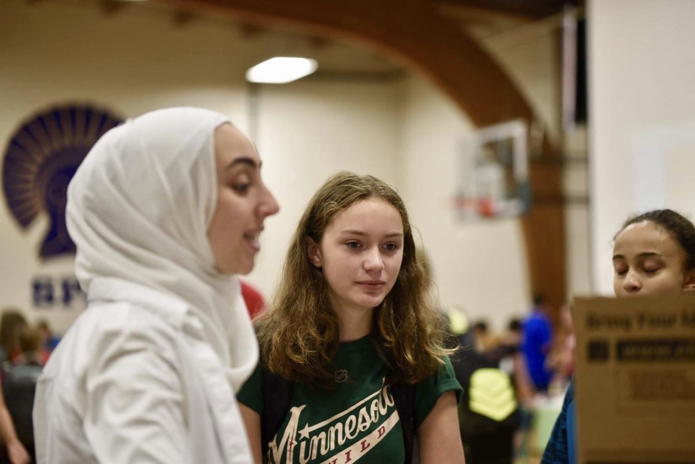 Senior and president of Muslim Student Alliance Iya Abdulkarim shows 9th grader Margot Bergner the MSA poster.