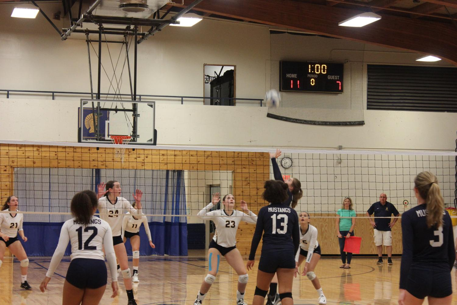 TEAMWORK. Players defend a spike from the Mustangs.
