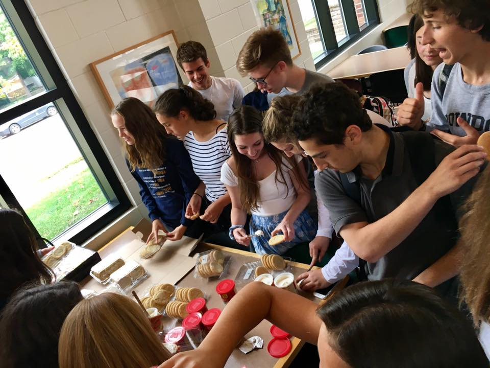 Students crowd around the table to decorate constitution themed cookies at the event.