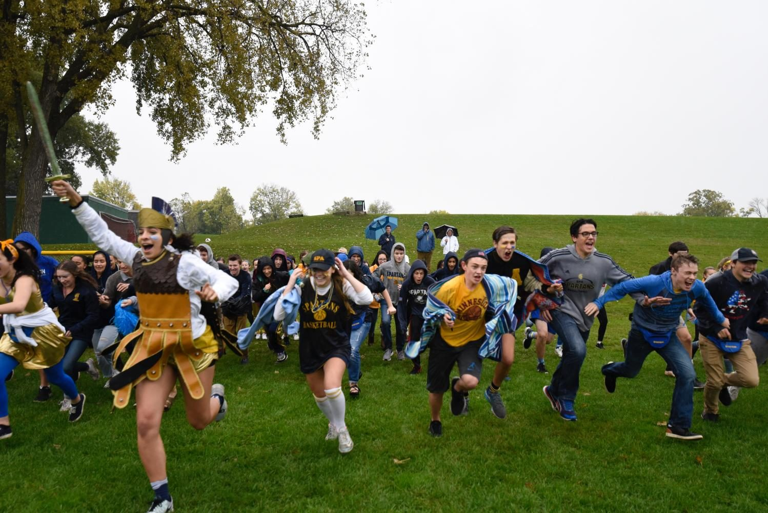 Senior and Spartan Izzy Denny leads students in the annual storming of the field. In spite of the rain, students turned out for the tradition.