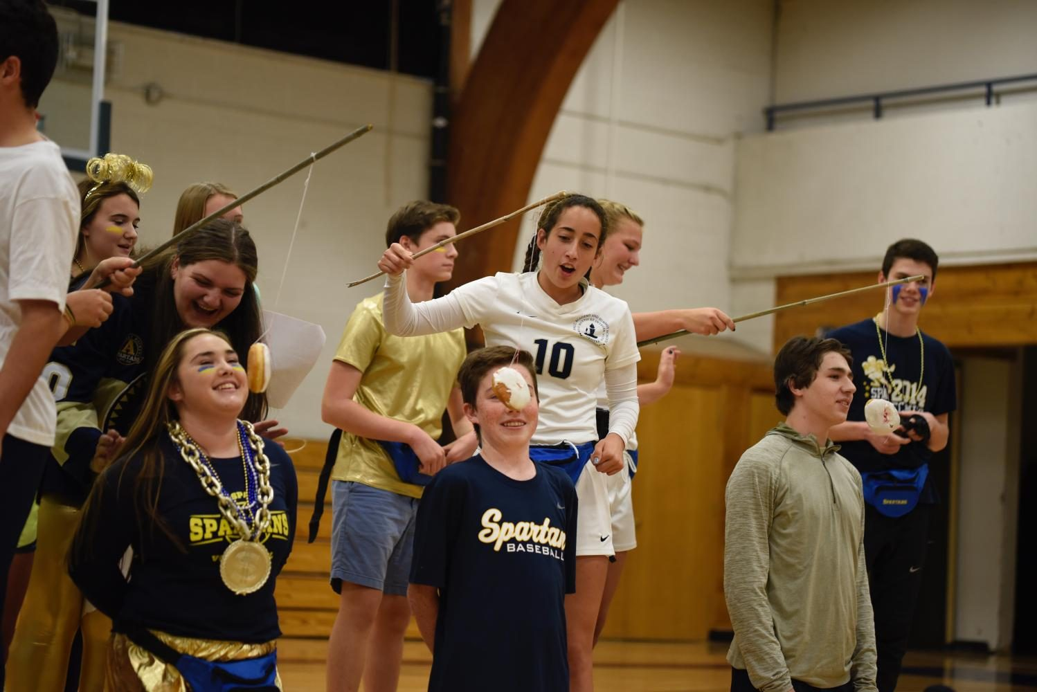 SAC members hold donuts on strings for student volunteers to compete and eat at Pep Fest.