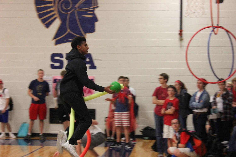Senior Noah Solomon flies through the air on his broom as he approaches the goal to shoot.