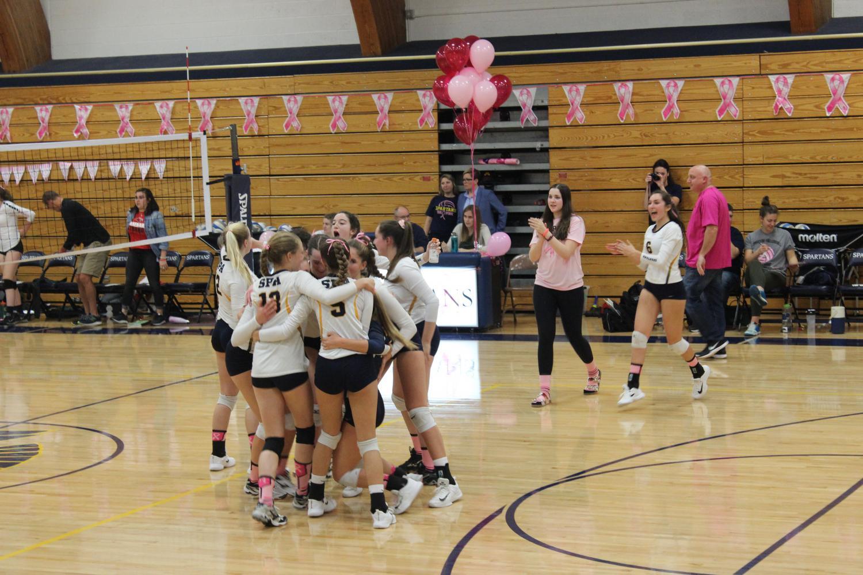 The varsity volleyball team celebrates their win against Minnehaha Academy.