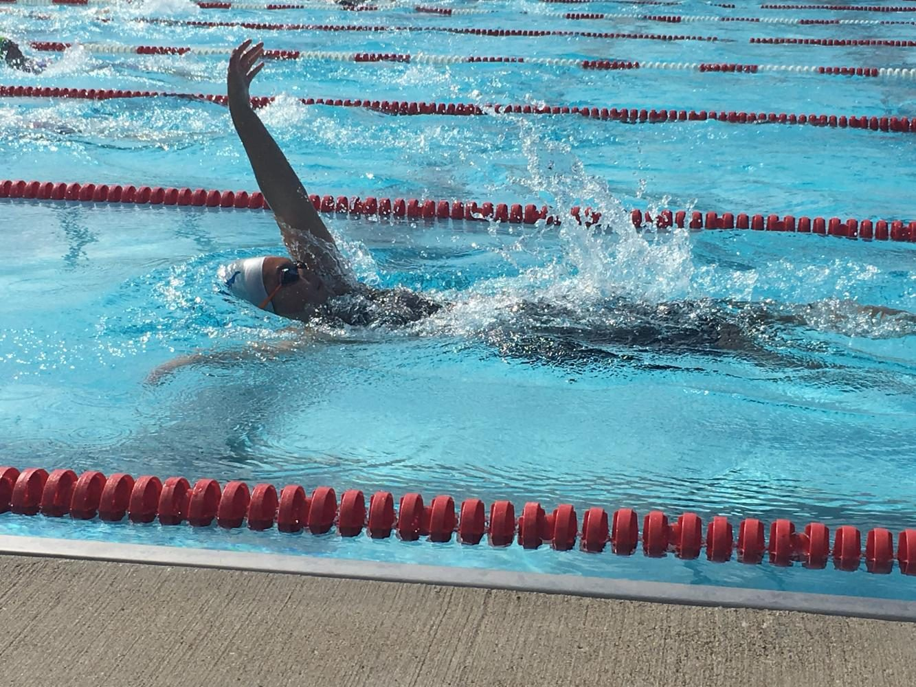 Ninth+grader+Jasmine+White+competes+in+the+backstroke+at+a+swim+meet.+White+has+been+swimming+since+first+grade+and+intends+to+continue+competing+in+college.+%22I%27m+still+too+young+to+apply+%5Bto+college%5D%2C+but+I%27m+already+looking+at+a+lot+of+different+schools+with+great+swimming+programs%2C%22+she+said.+