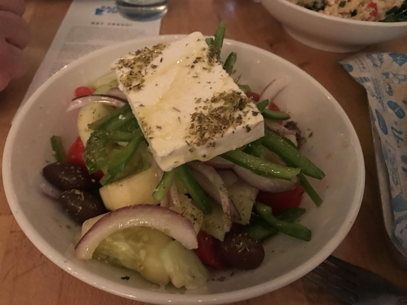The Greek salad with feta is served on top of mix of tomatoes, olives, green beans, and cucumbers.
