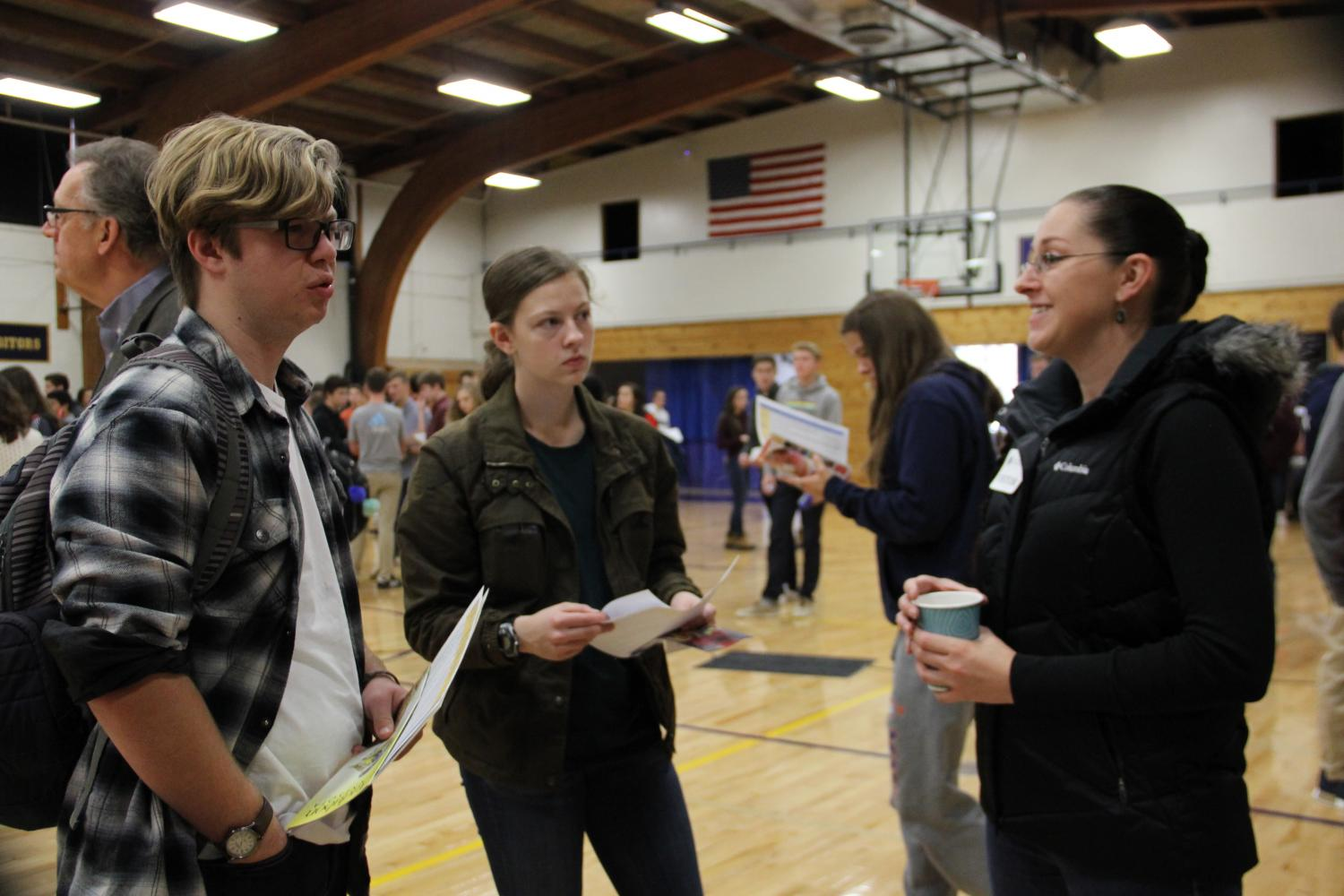 Students learn about the service opportunities available from a representative at the service fair.