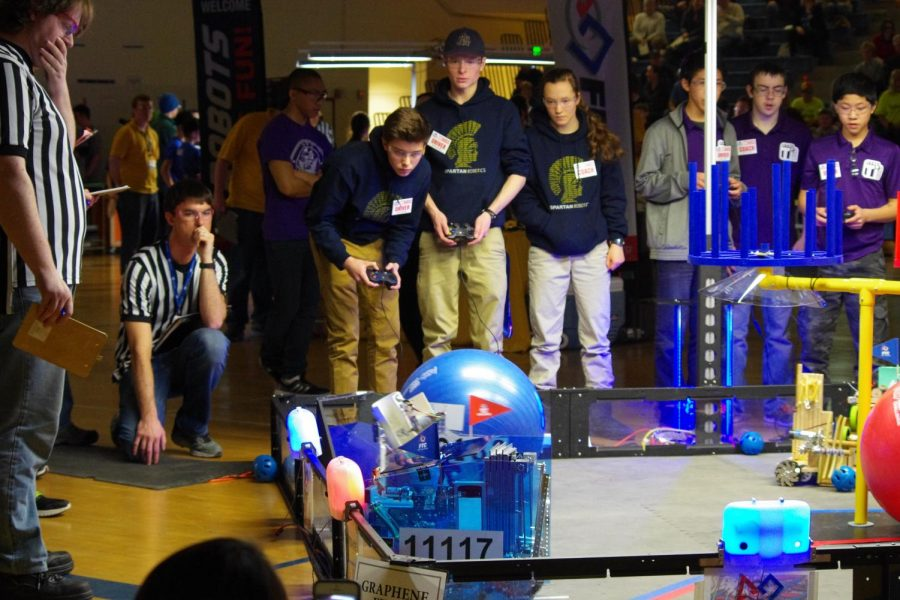 """Seniors Grant Gunderson and Michael Hall along with junior Michaela Polley watch their robot in a competition. """"For the first part of the competition the robot has to be pre-programmed and that's very challenging because there are so many things that can go wrong,"""" Hall said."""
