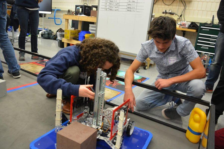 Junior Gabriel Konar-Steenberg and sophomore Gustav Baumgart examine a visitor's robot during an outreach even hosted by Spartan Robotics.