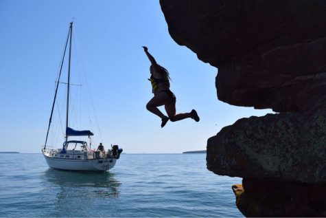 Ninth grader Emma Davies leaps from a cliff on Lake Superior after a day of sailing.