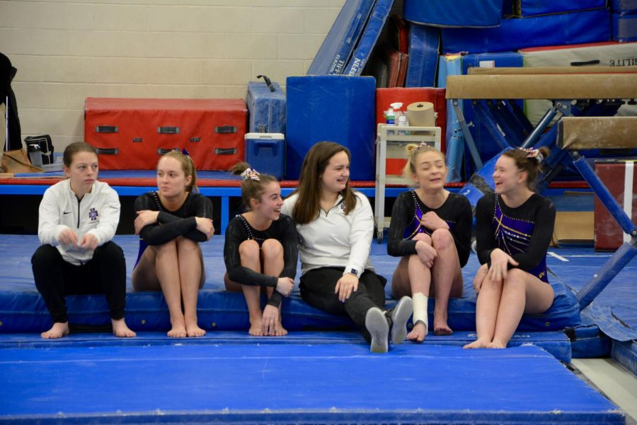 Gymnastics teammates sit together in their small but strong team during a break at the Roseville tournament.