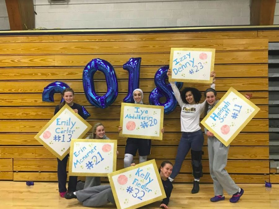 The Seniors on Girls Basketball pose with their signs after winning the game against Harding.