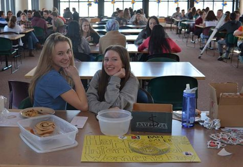 Seniors Erin McNamer and Isabel Brandtjen host a bake sale in the cafeteria to commemorate International Women's Day.