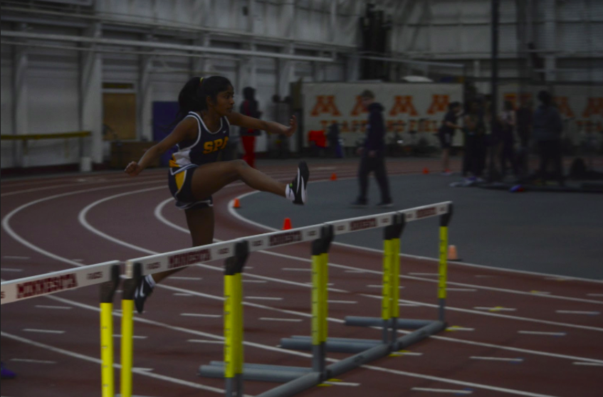 Ninth grader Rashmi Raveendran jumps a hurdle. Raveendran, Becca Richman, Sara Browne, and Olivia Lagos finished 2nd place in the 4x400m relay.