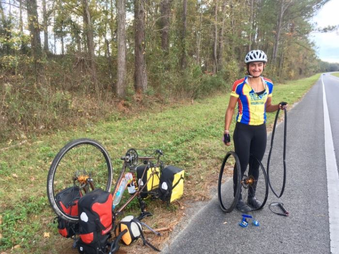 Alum+Ariana+Amini+%2813%29+poses+for+a+photo+next+to+her+bike+as+she+fixes+a+flat+tire.+Amini+is+part+of+an+all-female+team+biking+across+the+country+to+raise+awareness+for+protection+of+U.S.+public+lands.+%E2%80%9CNow+that+I%E2%80%99ve+immersed+myself+more+in+the+issue+I%E2%80%99ve+realized+how+convoluted+it+is%2C+and+how+many+perspectives+there+are%2C+and+aspects+that+affect+every+element+of+environmentalism%2C+Amini+said.