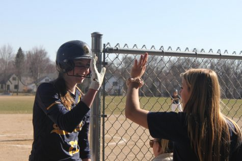 Sophomore Kathleen Bishop high fives senior Sophia Rose after scoring a run.