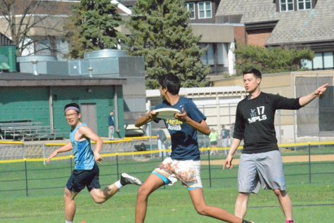 Senior Rahul Dev passes the disc to senior Larry Chen while US History teacher Ryan Oto guards on May 4 on Lang field.
