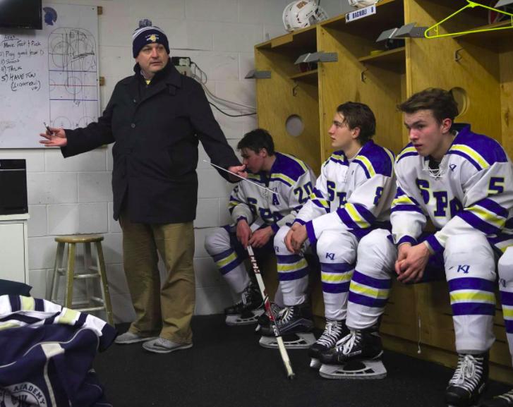 Former head coach Matt Funk coaches between periods during a game against Virginia High School.