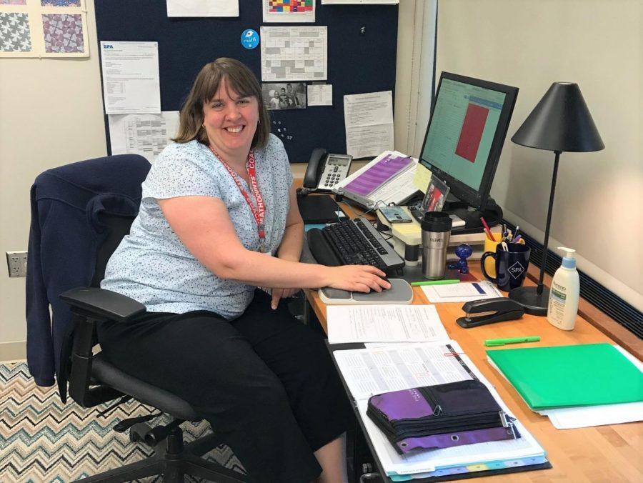 MS math teacher Jenny Borovsky sits at her desk surrounded by paper.