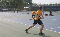 Senior Duke Nguyen returns his opponents serve.